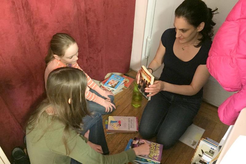 Maeve helps Gwynne and Devyn sort books into categories.